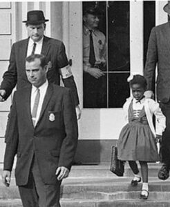 A young African American girl walks behind two white men in suits. She is carrying a school bag and wearing a dress and white sweater. The image is black and white.