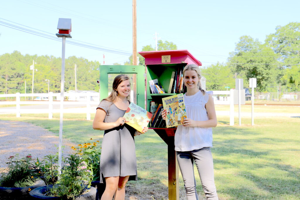 Two young women stand in front of a little lending library for books in a park. They are each holding a book and smiling.