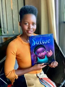 Lupita Nyong'o holds her book Sulwe. She is wearing an orange shirt and multicolored pants and sitting in a dark colored chair.